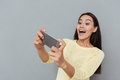 Happy excited young woman playing video games on cell phone Royalty Free Stock Photo