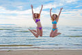 Happy excited young women in bikini jumping on beach Royalty Free Stock Photo