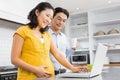 Happy expectant couple using laptop Royalty Free Stock Photo