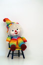 Happy faced clown doll sitting on a time out chair with blue yellow green orange clothing and hat with bow white wall and floor Stock Photo