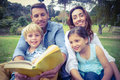 Happy familly reading a book in the park on sunny day Stock Photo