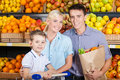 Happy family against shelves of fruits goes shopping father keeps a paper bag with and son sits in the cart Royalty Free Stock Photo