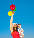 Happy family with air balloons holding colorful over blue sky background mother and adorable child baby boy playing games outdoor Royalty Free Stock Photos