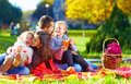 Happy family on autumn picnic in park the Stock Photography