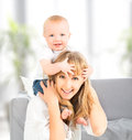 Happy family baby sits astride the shoulders of the mother a Royalty Free Stock Photo