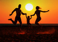 Happy family on the beach silhouette of jumping at sunset Stock Photo
