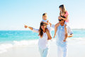 Happy family on the beach walking Stock Image