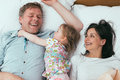 Happy family in bed having fun Stock Photography