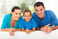 Happy family bed young of three lying on at home Stock Photos
