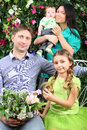 Happy family with bunch of flowers in garden four near verdant hedge Stock Image