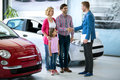 Happy family buy new car dealer handshaking with daddy congratulated the on a Royalty Free Stock Images