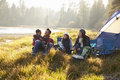 Happy family on a camping trip relaxing by their tent Royalty Free Stock Photo