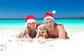 Happy family celebrating christmas on beach in santa hats Royalty Free Stock Images