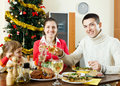 Happy family celebrating christmas over celebratory table of three at home interior Stock Photo