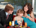 Happy family with child in cafe. Royalty Free Stock Image