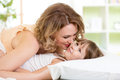 Happy family child and mother play kiss tickle baby laugh in white bed Royalty Free Stock Photo