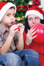 Happy family at christmas mother helps son to inflate balloons Stock Images