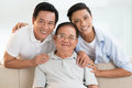 Happy family closeup portrait of three men generations smiling and looking at camera Stock Images