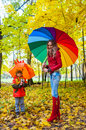 Happy family with colorful umbrellas in autumn park bright multicolored Stock Photography