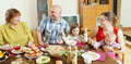 Happy family communicate over holiday table at home interior Royalty Free Stock Photography