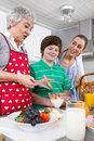 Happy family cooking together dessert with the grandmother Royalty Free Stock Photo