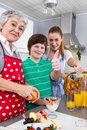 Happy family cooking together dessert with the grandmother Stock Photos