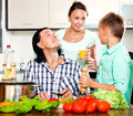 Happy family cooking veggy lunch couple with teenager son in home kitchen Royalty Free Stock Images