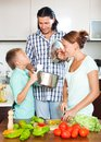Happy family cooking veggy lunch in home kitchen Royalty Free Stock Photo