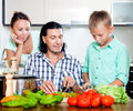 Happy family cooking veggy lunch with teenager son with fresh vegetables at home kitchen Royalty Free Stock Photography