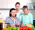 Happy family cooking veggy lunch with teenager son with fresh vegetables at home kitchen Stock Images