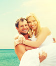 Happy family couple in love hugging and laughing on the beach young at sea Stock Photo