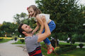 Happy family Dad throws child daughter up on a walk  in park Royalty Free Stock Photo