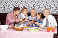 Happy family at dinner table clinking glasses of red wine Royalty Free Stock Photography
