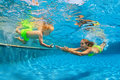 Happy family diving underwater with fun in swimming pool Royalty Free Stock Photo