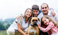 Happy family with a dog enjoying the countryside lifestyle Royalty Free Stock Photo