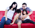 Happy family enjoy time at red sofa isolated asian is enjoying their weekend break on white background Royalty Free Stock Photography