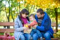 Happy family enjoying autumn picnic. Father mother and son sit o Royalty Free Stock Photo