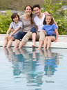 Happy family lying by the swimming pool