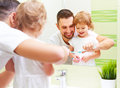 Happy family father and child girl brushing her teeth in bathroo Royalty Free Stock Photo