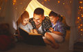 Happy family father and children reading a book  in  tent at hom Royalty Free Stock Photo
