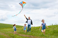 Happy family father and children run with kite on meadow Royalty Free Stock Photo