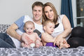 Happy family of father, mother and baby playing in bed Royalty Free Stock Photo