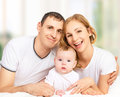 Happy family of father mother and small baby girl daughter in white bed Stock Image