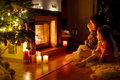 Happy family by a fireplace on christmas young mother and her two little daughters sitting in cozy dark living room eve Royalty Free Stock Image
