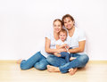 Happy family on floor near empty wall in the apartment bought on mortgage blank Royalty Free Stock Photography