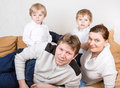 Happy family of a four having fun at home in blue jeans and white shirts Stock Images