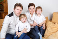 Happy family of a four having fun at home in blue jeans and white shirts Royalty Free Stock Photos
