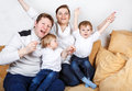 Happy family of a four having fun at home in blue jeans and white shirts Royalty Free Stock Photography