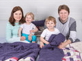 Happy family of a four having fun at home in pajamas in bed Royalty Free Stock Photos