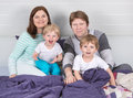 Happy family of a four having fun at home in pajamas in bed Stock Photography
